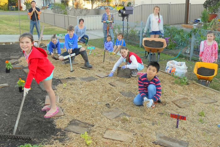 Neighbourhood kids creating a community verge veggie garden. Graeme Stuart.