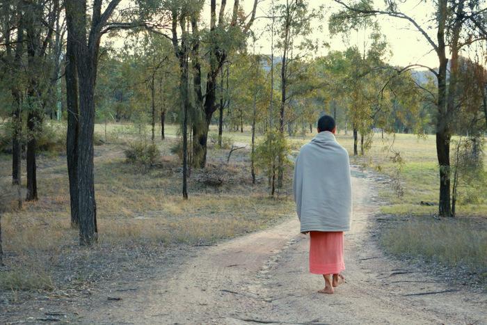 Barefoot buddhist monk walking. Little eco footprints