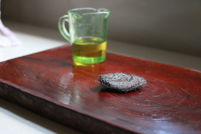 Restoring a timber chopping board with vegetable oil and steel wool. Little eco footprints.