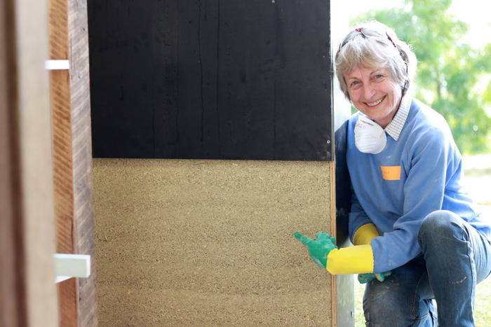 Shepherds Ground member Angela Rath with a hemp masonry wall that she helped to build. Little eco footprints